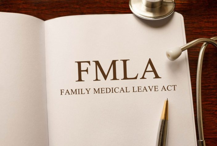 Page with FMLA (Family Medical Leave Act) on the table with stethoscope, medical concept