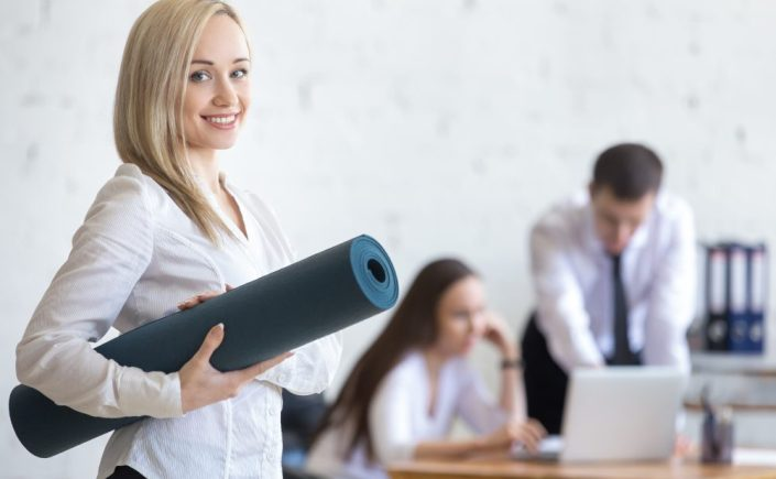 Business woman posing with exercise mat